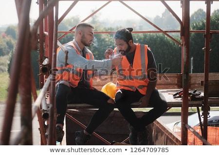 Construction travailleurs fumer cigarette parler pause Photo stock © diego_cervo