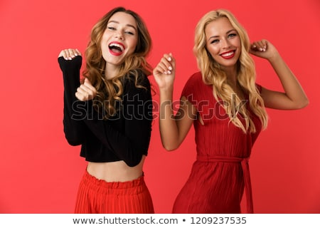 Excited young friends women standing isolated over red background dancing. Stock photo © deandrobot