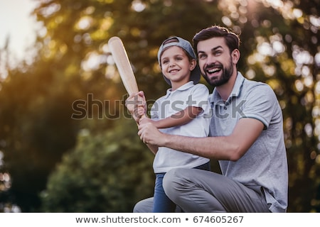 Handsome dad with his little cute sun are playing baseball on green grassy lawn Stock photo © Lopolo