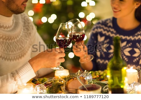 happy couple drinking red wine at christmas dinner stock photo © dolgachov