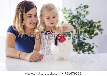 Little girl and his mother inserting money into piggy bank. Stock photo © Lopolo