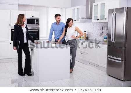 Real Estate Agent Showing Refrigerator In House To A Couple Stock photo © AndreyPopov
