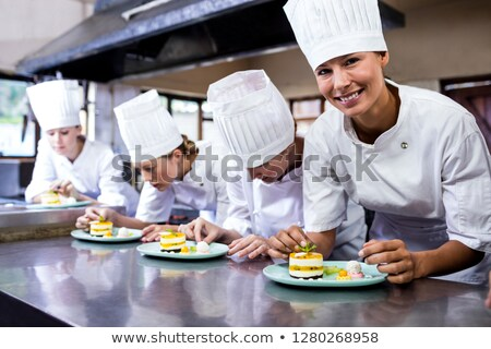 Group of chefs garnishing delicious desserts in a plate at hotel Stock photo © wavebreak_media