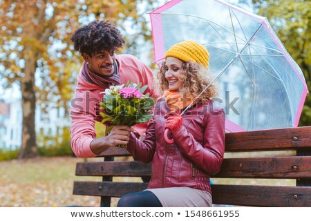 man surprising his wife with a bouquet of flowers on a drizzly fall day stock photo © kzenon