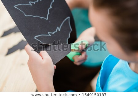 hands of elementrary schoolgirl with scissors cutting out bat from black paper stock photo © pressmaster