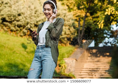 Pretty, young woman with headphones outdoors, in a lovely park Stock photo © lightpoet