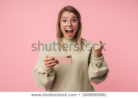 Portrait of delighted woman playing game on cellphone and screaming Stock photo © deandrobot