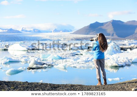 Photographer tourist woman taking photos with DSLR camera on travel on Iceland by Jokulsarlon glacia Stock photo © Maridav