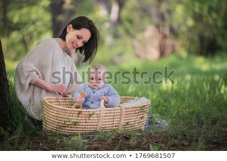 Child sits on mother, who lies on grass Stock photo © Paha_L