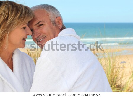 Older couple smooching in the sand dunes Stock photo © photography33