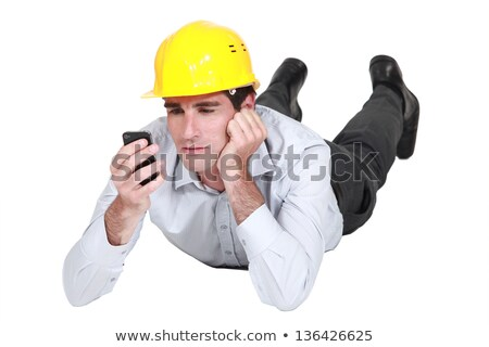 architect lying on floor looking annoyed at sms Stock photo © photography33