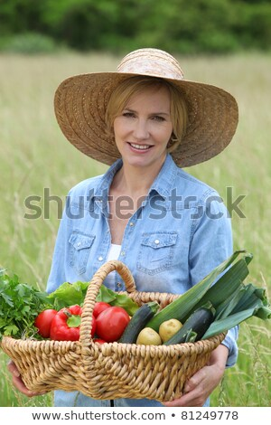 woman stood in field carrying basket of vegetables stock photo © photography33