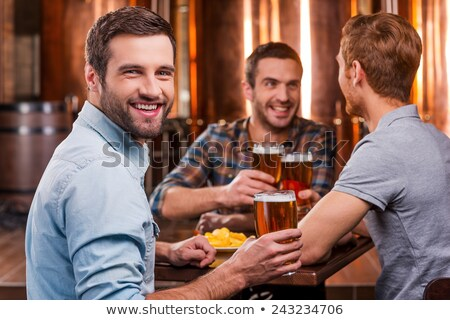 handsome young man toasting with beer in a pub stock photo © nejron
