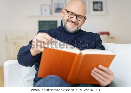 middle aged man relaxing with book sitting on sofa stock photo © monkey_business