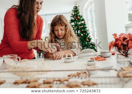 Woman baking Christmas cookies in her kitchen Stock photo © HASLOO