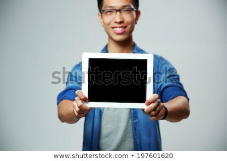 Happy asian man showing tablet computer screen on gray background. Focus on tablet computer Stock photo © deandrobot