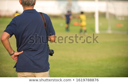 father watching son playing soccer game stock photo © stevanovicigor