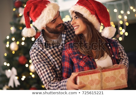 lovely christmas couple in santa claus hats stock photo © master1305
