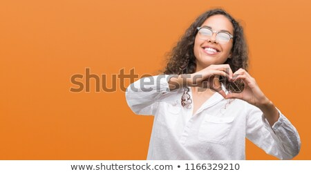 smiling young woman in shirt showing heart shape Stock photo © dolgachov