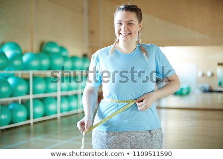 happy young plus size woman with measuring tape Stock photo © dolgachov