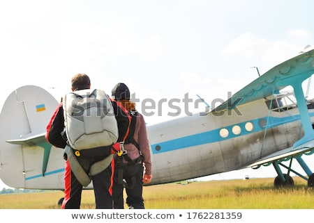 Woman walking across the field with plane on the background Stock photo © deandrobot