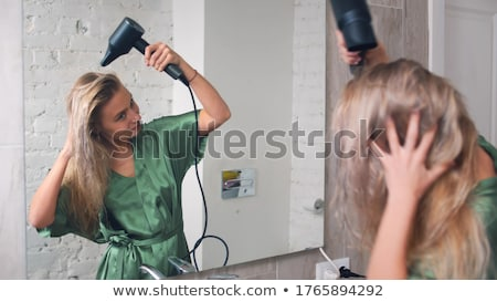 Beautiful girl drying her hair with Hairdryer Stock photo © rogistok