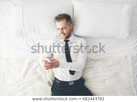 Top view. Handsome businessman lying on bed texting from his smartphone Stock photo © tommyandone