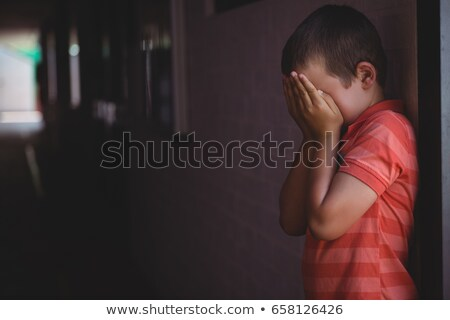 Boy covering his face with hands while standing in corridor Stock photo © wavebreak_media