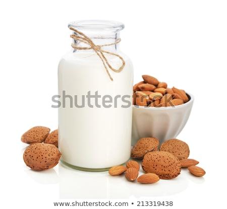 Almond nuts and milk on white background Stock photo © yelenayemchuk