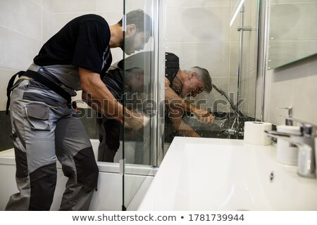 Man using wrench to fix bathtub Stock photo © IS2