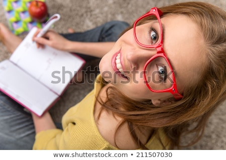 portrait of beautiful smiling woman in glasses taking notes whil stock photo © deandrobot
