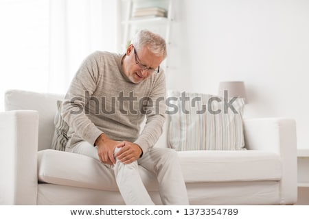 unhappy man suffering from pain in leg at home Stock photo © dolgachov