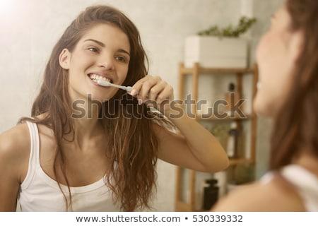 Mosolygó nő fogmosás közelkép mosoly boldog fürdőszoba Stock fotó © Kzenon