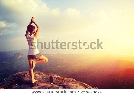 Puesta de sol yoga acantilado femenino movimiento pie Foto stock © lovleah