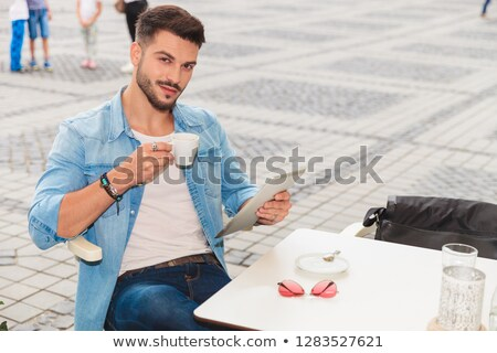 Stock photo: handsome man holds tablet while taking coffee break in city