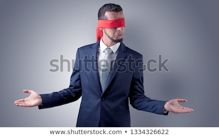 Stock photo: Covered eye businessman in front of a wall