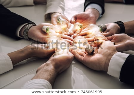 Teamwork and brainstorming concept with businessmen that share an idea with a lamp. Concept of start Stock photo © alphaspirit