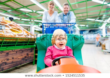 Stock photo: Couple shopping in supermarket using a special child trolley
