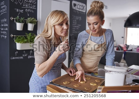 mother and daughter cooking cupcakes at home stock photo © dolgachov