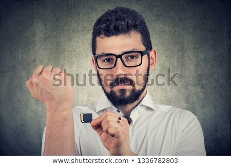 Young man holding a microchip willing to implant it under the skin  Stock photo © ichiosea
