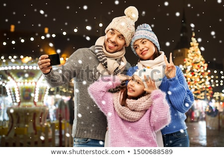 mother picturing daughter by phone on christmas Stock photo © dolgachov