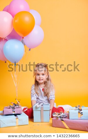 Little casual cutie with gift posing on yellow background Stock photo © pressmaster