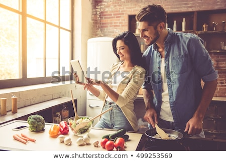 beautiful young couple smiling while cooking in kitchen at home stock photo © boggy