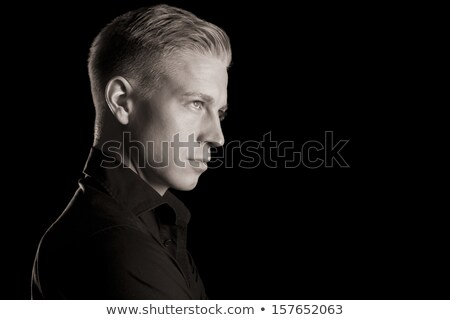 Black and white portrait of young likable man, low key. Stock photo © lichtmeister