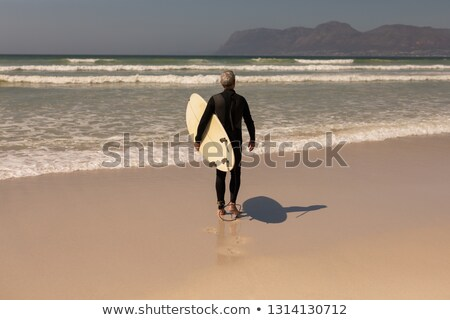 rear view of senior male surfer walking with surfboard on the beach with mountains in the background stock photo © wavebreak_media