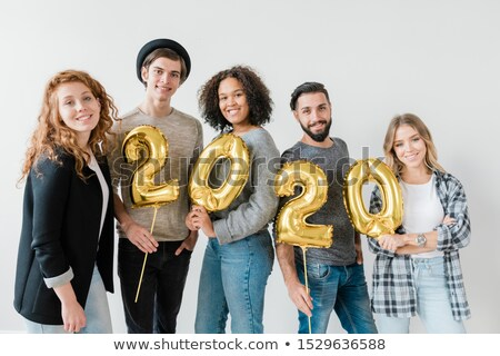 Group of multicultural friends holding golden balloons in form of numbers Stock photo © pressmaster