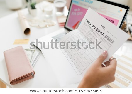 Female hand holding paper with checklist after making order in online shop Stock photo © pressmaster