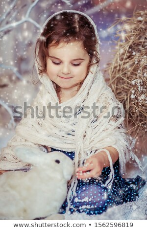 Little girl dressed in vintage winter tradition against artificial snow and forest background Stock photo © ElenaBatkova