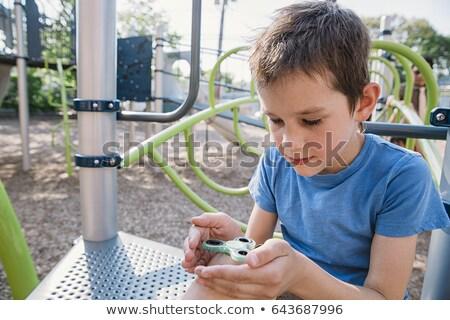Boy playing with fidget spinner. Child spinning spinner on the playground. Blurred background Stock photo © galitskaya