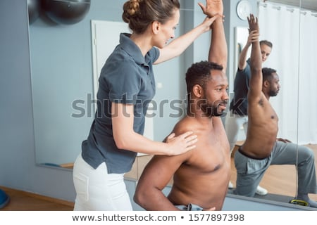 Young man receiving physical therapy after sport injury Stock photo © Kzenon